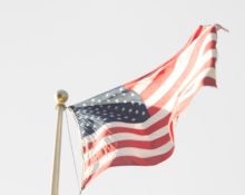 American Flag waving from top of flagpole. Photo by Maureen McEvers.