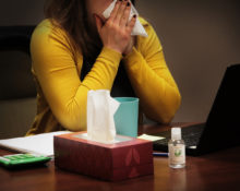 Woman sitting at a desk blowing her nose.