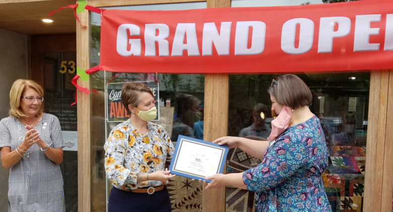 Quilts by Commission Owner Stephanie McCall, at right, receives a certificate from CEDA Business Development Specialist Meg Goloub while Senator Pam Helming looks on during a grand opening ceremony September 18, 2021, at the business's new location at 53 Genesee Street in downtown Auburn. Stephanie received assistance from CEDA in acquiring a loan from the City of Auburn's Small Business Assistance Program.